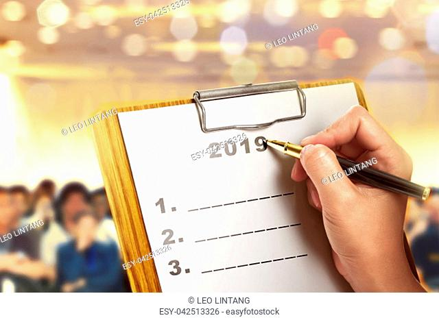 Businessman write a list for 2019 on the paper. List for 2019. Happy New Year 2019