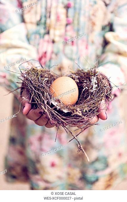 Girl holding an egg in a nest