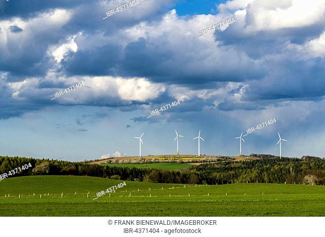 Agricultural landscape with wind power plants, trees, green fields and cloudy blue sky, Hausdorf, Saxony, Germany