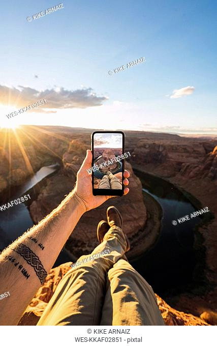 USA, Arizona, Colorado River, Horseshoe Bend, young man on viewpoint, holding smartphone