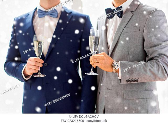 people, celebration, homosexuality, same-sex marriage and love concept - close up of married male gay couple in suits and bow-ties drinking sparkling wine from...