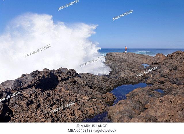 Tourist observes waves on the coast from la Fajana, Barlovento, Canary islands, Spain