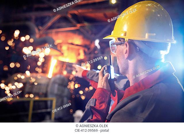 Steelworker talking, using walkie-talkie in steel mill