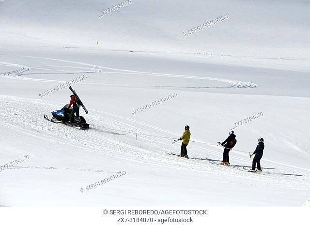 Baqueira Beret, Ski resort, Pyrenees, Aran Valley, Lleida, Catalonia, Spain. Line of people skiing with snowmobile