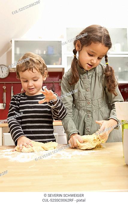 Children kneading dough in kitchen