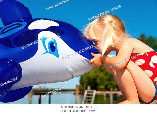 Girl kissing inflatable whale on dock