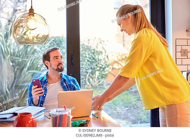 Woman tidying dining table whilst husband using smartphone