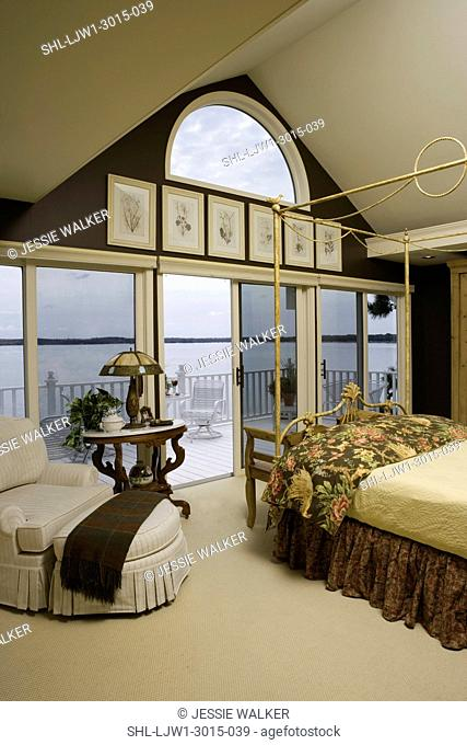 MASTER BEDROOM: dark brown painted walls, metal four poster bed in mustard colors, floral bedding, looking out a wall of sliding doors to upper deck, lake view