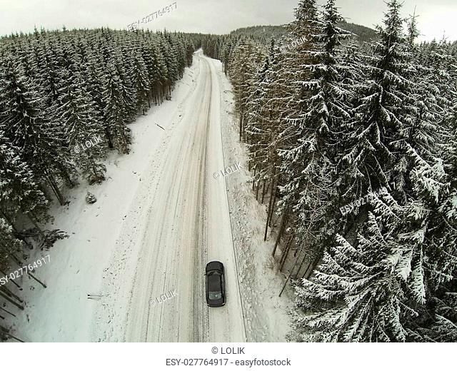 Aerial shot of snow-covered road in the countryside Carpathian Mountains with car on way