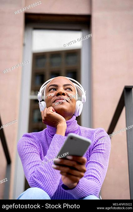 Portrait of white haired woman with white headphones and stickers in her face listening to music and laughing