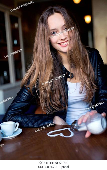 Portrait of happy mid adult woman pouring sugar heart on cafe table