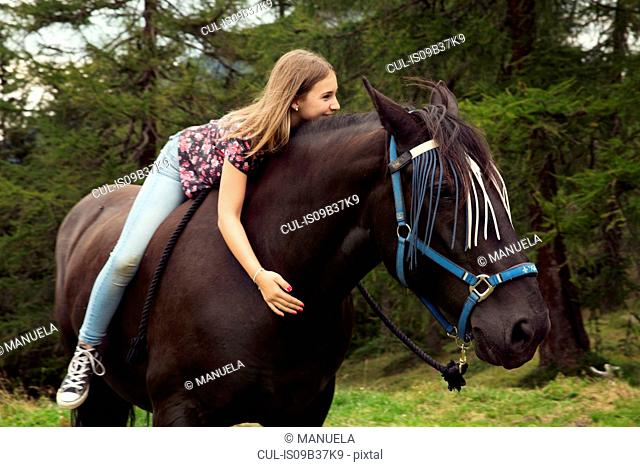 Girl sitting bareback on horse in forest glade, Sattelbergalm, Tyrol, Austria
