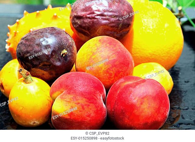 Exotic fruits: orange, kiwano, loquat, peach and passionfruit