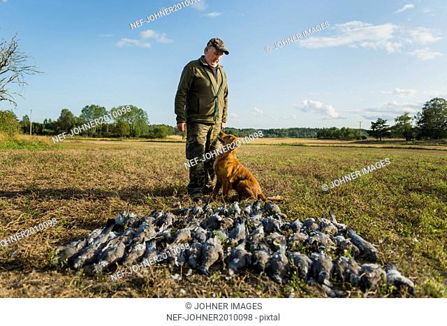 Man with hunting dog and dead birds