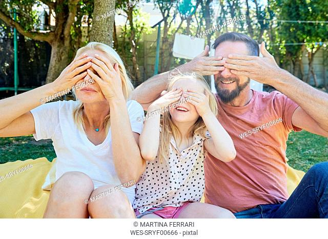 Portrait of happy family covering their eyes