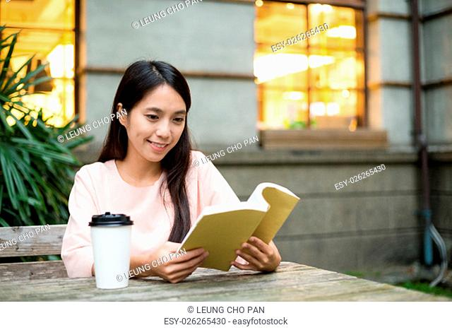 Woman reading book at outdoor coffee shop