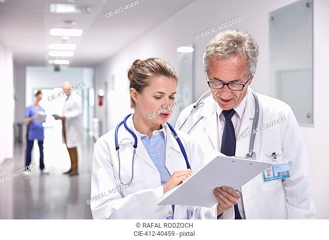 Doctors with clipboard making rounds, talking in hospital corridor