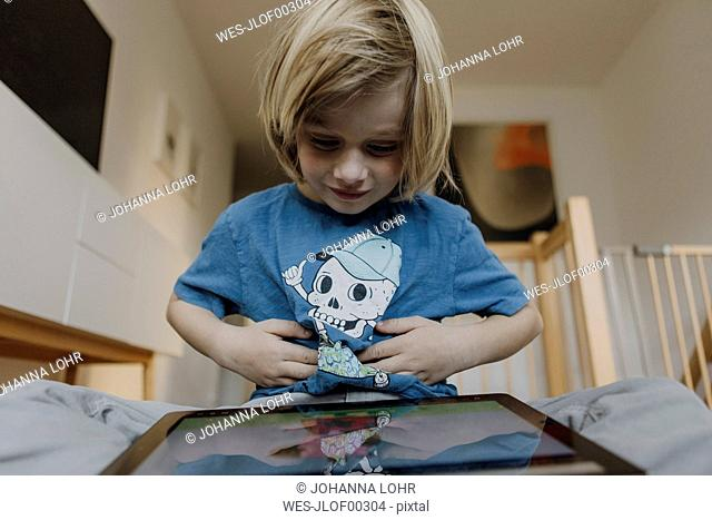 Portrait of content little boy using digital tablet at home