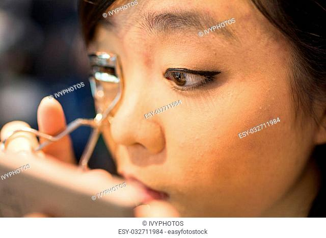 Young Asian woman fixing her eye lash with clipper