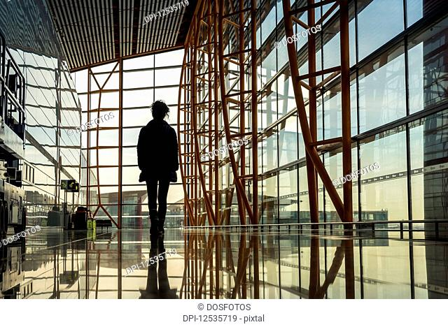 Passenger standing in airport terminal building looking out the window, Beijing Capital International Airport; Beijing, China