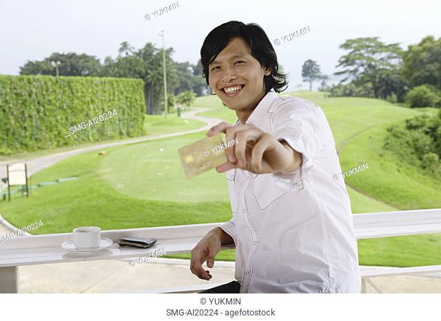 Man holding credit card, smiling at camera, golf course behind him