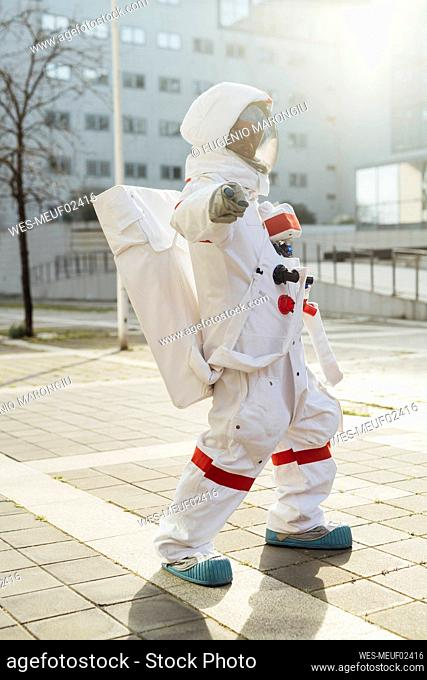 Female astronaut pointing while standing on footpath outside building