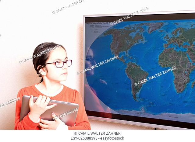 Little cute girl using at home a Tablet PC and an interactive television for homework