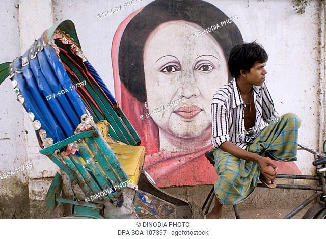 Cycle Rickshaw Rider with the wall painting of Begum Khaleda ; Dhaka; Bangladesh