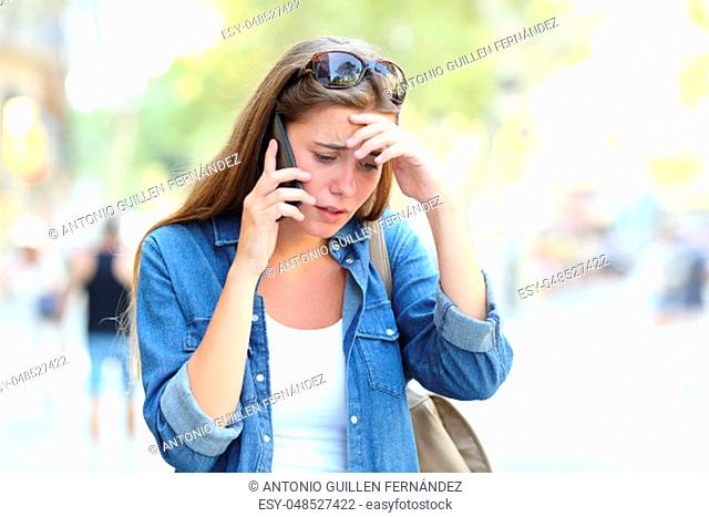 Worried woman having a mobile phone conversation walking in the street