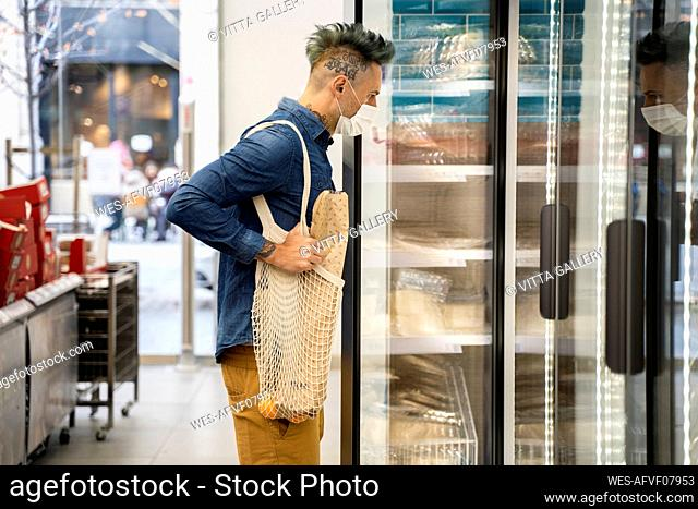 Stylish man looking in display cabinet at supermarket