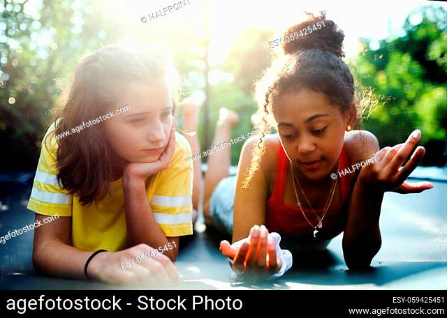 Front view of cheerful young teenager girls friends outdoors in garden, talking
