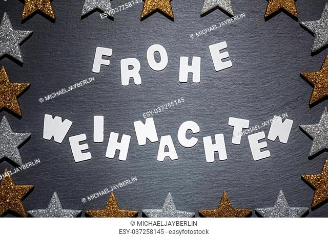 German language Christmas wish, white letter text on dark slate backround with golden and silver star frame