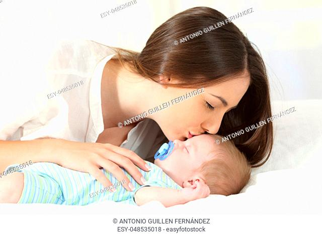 Side view portrait of an affectionate mother kissing her baby sleeping on a bed