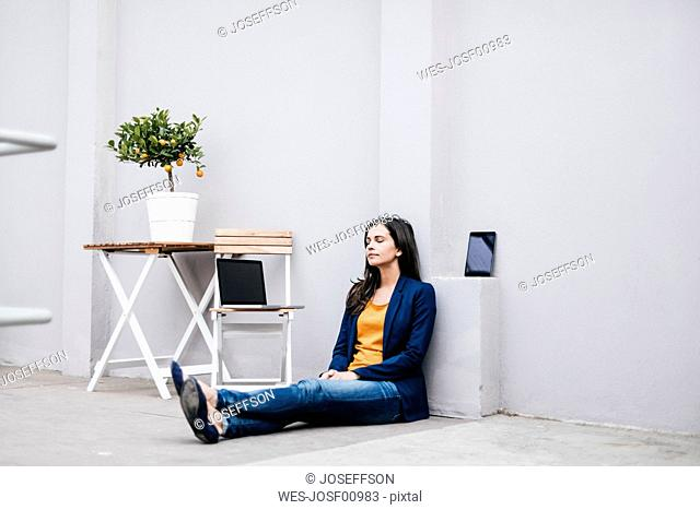 Businesswoman sitting on the floor relaxing