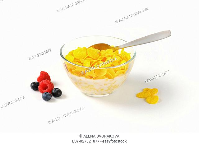 bowl of corn flakes with fresh milk on white background