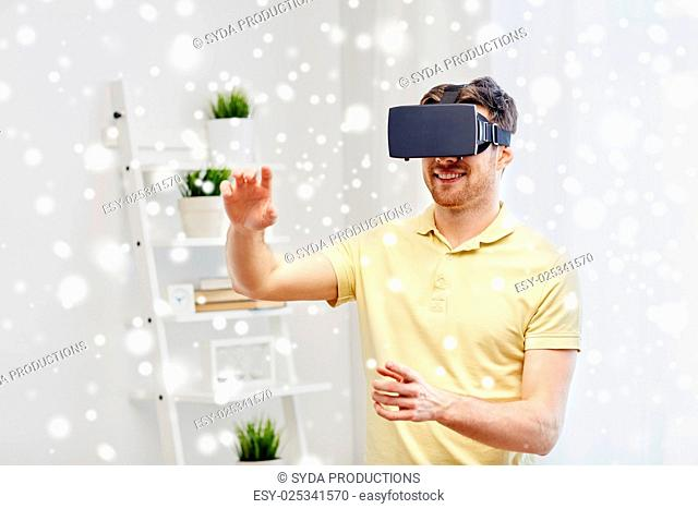 technology, augmented reality, gaming, entertainment and people concept - happy young man with virtual headset or 3d glasses playing video game at home over...
