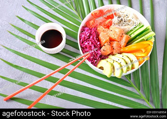Fresh seafood recipe. Organic food. Fresh salmon poke bowl with crystal noodles, fresh red cabbage, avocado, cherry tomatoes. Food concept poke bow