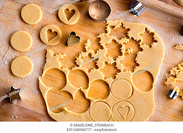 Cutting out circle and star shapes from rolled out dough to prepare traditional Linzer Christmas cookies