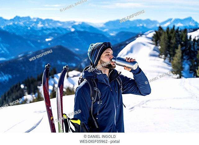Germany, Bavaria, Brauneck, man on a ski tour in winter in the mountains having a break drinking from thermos flask