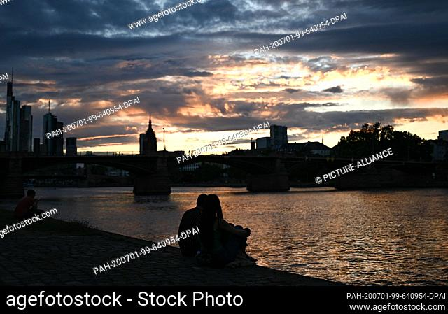 01 July 2020, Hessen, Frankfurt/Main: A couple watches the sunset on the banks of the Main in the evening. Photo: Arne Dedert/dpa