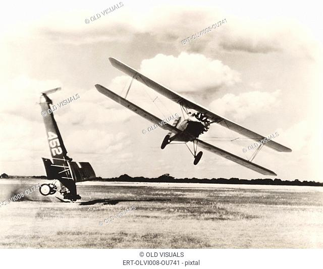Biplane flying past crash on field