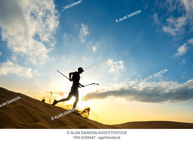 62 year old trail runner training on sand dunes at sunrise at Maspalomas, Gran Canaria, Canary Islands, Spain