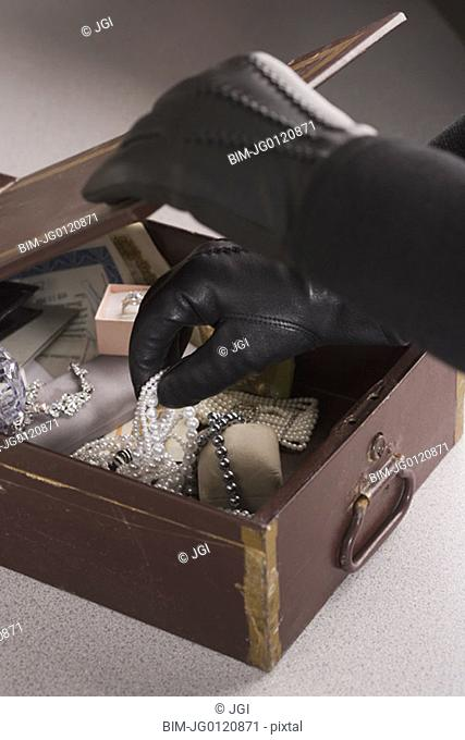 Close up of gloved hands taking jewels out of box