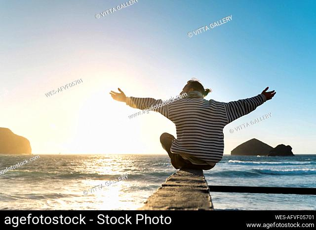 Man sitting at the coast at sunset with outstretched arms, Sao Miguel Island, Azores, Portugal