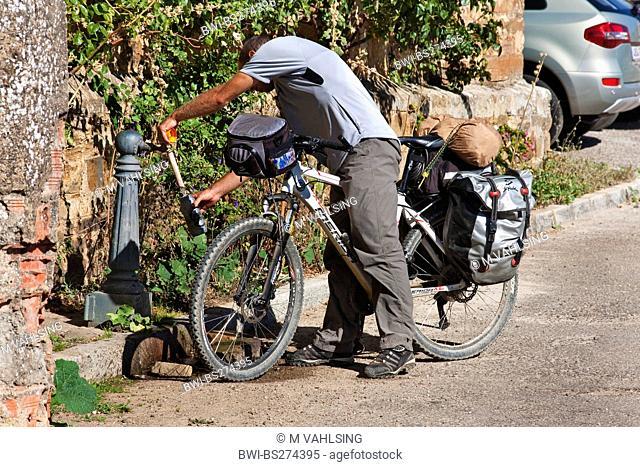 bicycle pilgrim filling up his waterbottle, Spain, Kastilien & Len, Leon, El Ganso