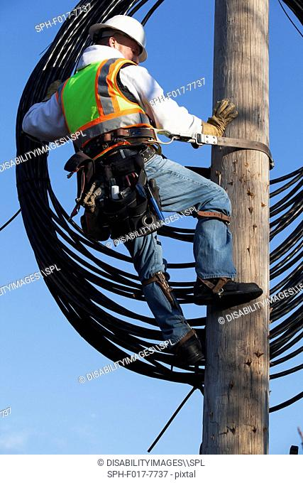 Cable lineman raising new cable up onto power pole