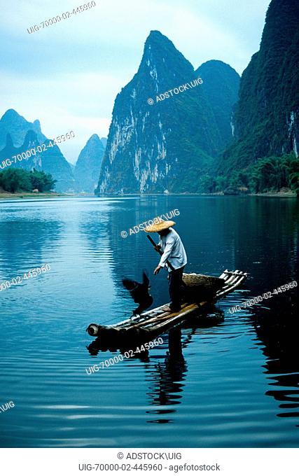 Li River, Guangxi, China: Cormorant fisherman on bamboo raft on river near Xingping Guilin area