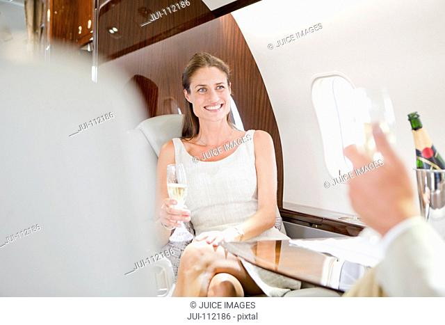 Attractive smiling woman drinking champagne on private jet
