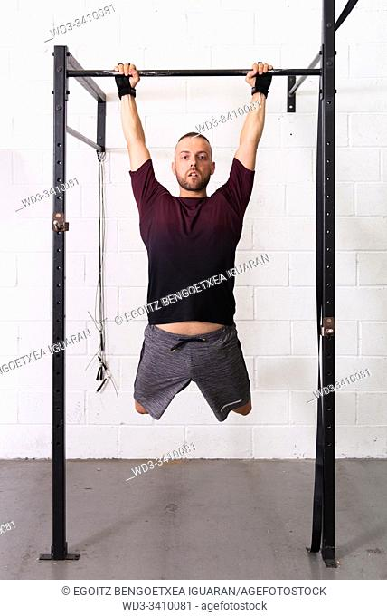 Young man making pull-ups with white background