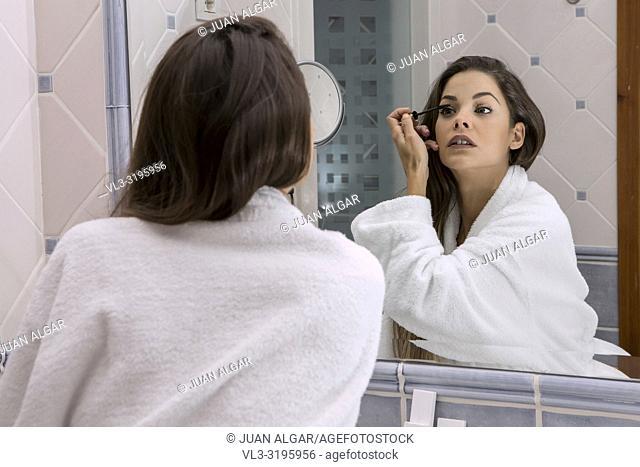 Beautiful brunette in white soft bathrobe looking at mirror and applying mascara on eyelashes
